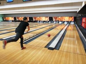 Une personne lance une boule sur la piste de Bowling.