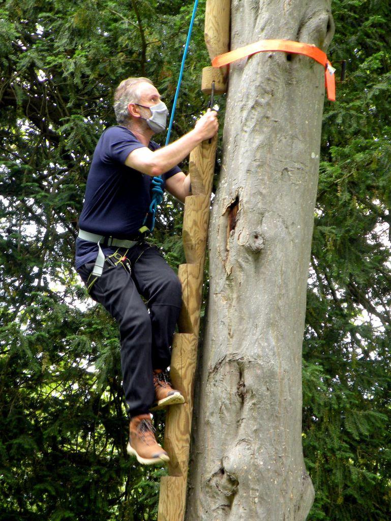 fabrice en pleine activité d'escalade où une partie d'un mur d'escalade est  installé contre un arbre